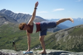 Jenny in Half Moon Pose (Ardha Chandrasana) atop Whistler Mountain in Jasper National Park, Alberta.  Then begin to lift the gaze, take the arm up, and press back with the lifted leg and foot (Photo by Ian Hatter).