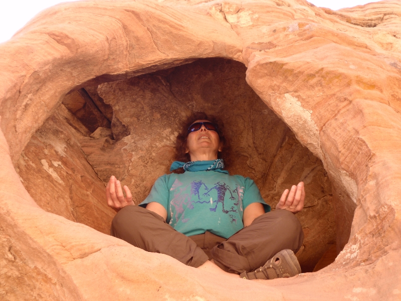 Jenny meditating in Easy Pose (Sukasana) in a red sandstone alcove in Valley of Fire State Park, Nevada (Photo by Ian Hatter).
