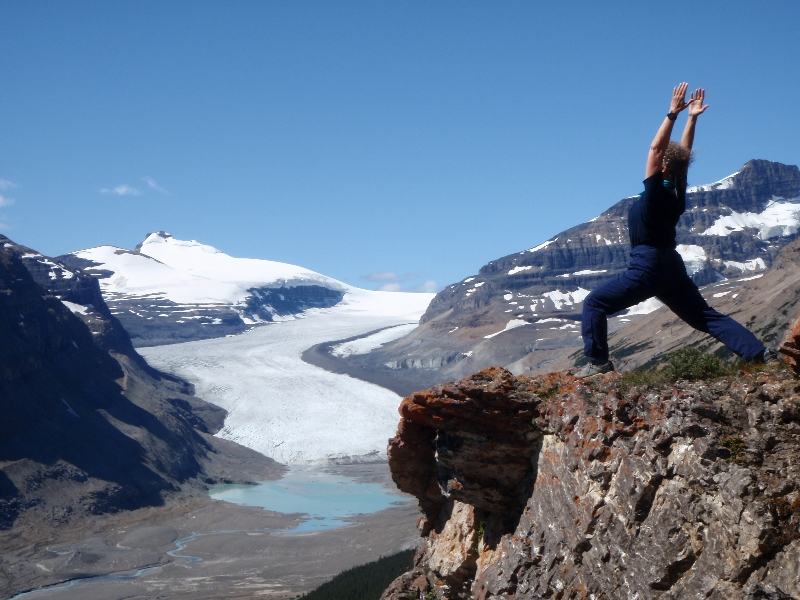 Jenny in Warrior One Pose (Virabhadrasana I) on Parker Ridge, with the Saskatchewan Glacier behind, Banff National Park, Alberta (Photo by Ian Hatter).