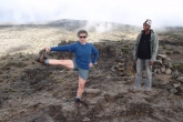 Jenny demonstrating how to do Standing Extended Hand to Big Toe Pose (Utthita Hasta Padangustasana) to our Assistant Guide Raymond Stephen Kanyama while on a short break during the climb up Mount Kilimanjaro, Tanzania (Photo by Ian Hatter).