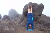 Jenny doing a supported Handstand (Adho Mukha Vrksasana), with a little help from a boulder on the foggy summit of Mount Angeles, Olympic National Park, Washington State. To ready oneself for moving the feet away from the prop, provide structural stability by looking forward, pressing down through the fingers and hands, and aligning joints (Photo by Ian Hatter).