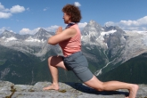 Jenny in Low Lunge (Anjaneyasana) with hands in prayer position (Namaste) at Abbott Ridge, with Mount Sir Donald in the background, Glacier National Park, B.C. (Photo by Ian Hatter)