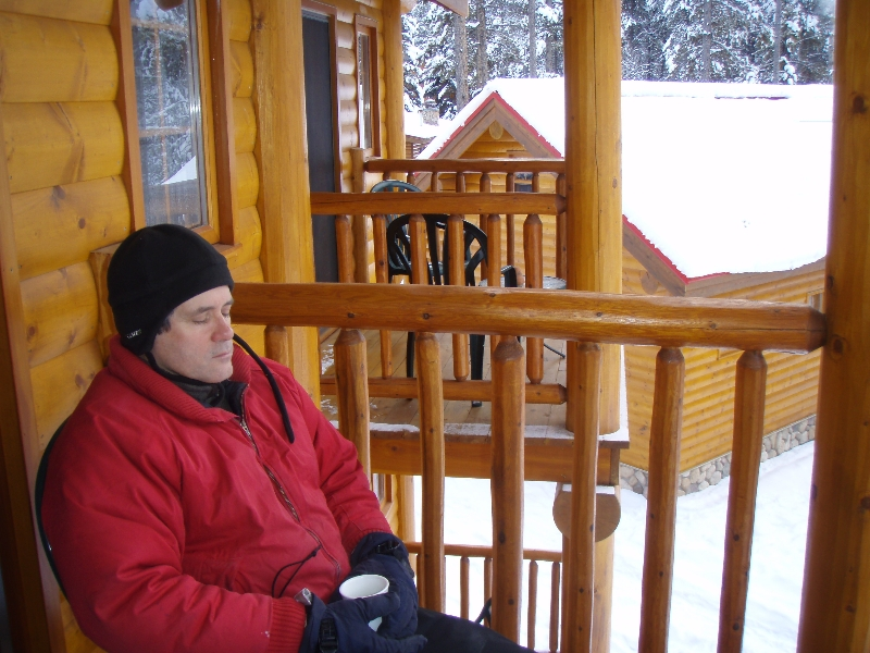 Ian meditating in the fresh subzero mountain air outside of Baker Creek Chalet, Banff National Park, Alberta. He is aided by a chair and the Coffee Mudra (Photo by Jenny Feick).
