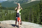 Ian assisting Jenny with Handstand (Adho Mukha Vrksasana) near the Giant Steps along the Paradise Valley Trail below Mount Temple, in Banff National Park, Alberta.  Ian provides a hand on the back of one of her ankles that she can use to press against to lift her leg upright and to maintain her alignment (Photo by Gwen Smiley).