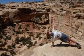 Jenny in Side Plank Pose (Vasisthasana) with the gaze upward, above the Hickman Bridge in Capitol Reef National Park, Utah (Photo by Ian Hatter).