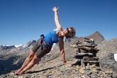 Jenny in Side Plank Pose (Vasisthasana) with the gaze and side body facing upwards, atop Paget Peak, Yoho National Park, B.C. (Photo by Ian Hatter).