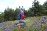 Jenny in Warrior One Pose (Virabhadrasana I), hampered somewhat by her daypack in her effort to lift the chest skyward, among the wild Camas (Camassia) meadows at the summit of Mount Benson above Nanaimo, Vancouver Island, B.C. (Photo by Ian Hatter).