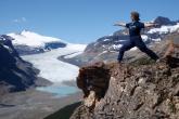 Jenny in Warrior Two Pose (Virabhadrasana II) on Parker Ridge, Sakatchewan Glacier behind, Banff National Park, Alberta (Photo by Ian Hatter)