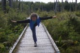 Jenny getting into Warrior Three Pose (Virabhadrasana III) along a boardwalk in Pacific Rim National Park, Vancouver Island, B.C. (Photo by Ian Hatter).