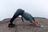 Jenny in Downward Facing Dog (Adho Mukha Svanasana) on top of the Barranco Wall on Mount Kilimanjaro, Tanzania, Africa (Photo by Ian Hatter)