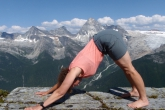 Jenny in Downward Facing Dog (Adho Mukha Svanasana) on Abbot Ridge in Glacier National Park, B.C.  across from Mount Sir Donald (Photo by Ian Hatter)