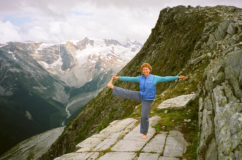 Jenny in Extended Hand to Big Toe Pose (Utthita Hasta Padangustasana) at her favourite place in the world to do yoga on Abbott Ridge, Glacier National Park, B.C. (Photo by Ian Hatter).