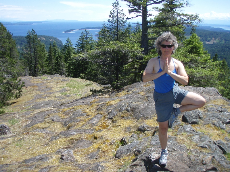 Jenny in Tree Pose (Vrikshasana) hands in prayer position (Anjali Mudra), on top of the South Peak of the Chinese Mountains on Quadra Island, B.C.(Photo by Ian Hatter).