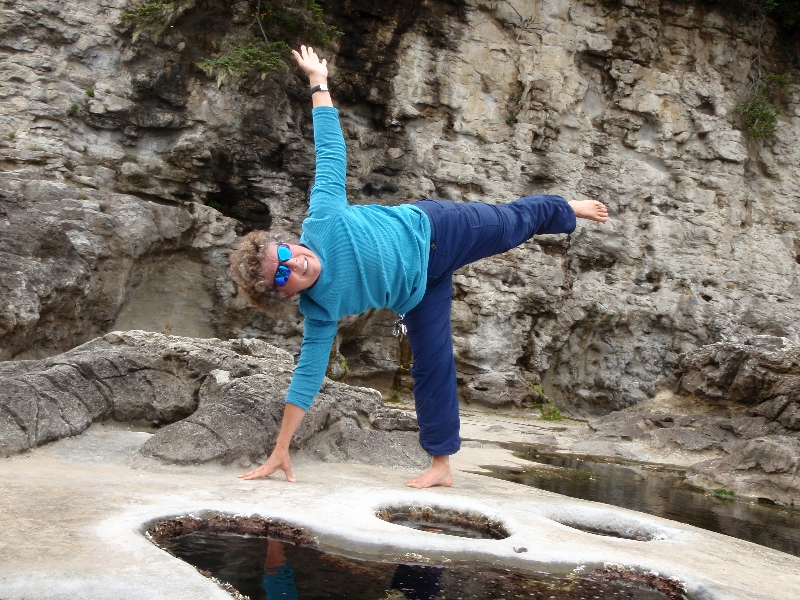 Jenny in Half Moon Pose (Ardha Chandrasana) at Botanical Beach, Juan de Fuca Provincial Park, Vancouver Island, B.C. Eventually the gaze, upper arm and chest face up, with the neck and crown of the head in line with the torso and lifted leg.  The stability comes from the pressing back of the lifted leg and sole of the foot (Photo by Ian Hatter).