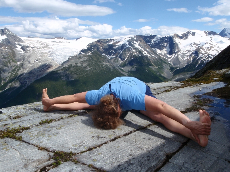 Jenny in Seated wide Legged Forward Fold (Upavistha Konasana) on Abbot Ridge, Glacier National Park, B.C.  (Photo by Ian Hatter).