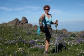Jenny in position one of the full Standing Extended Hand to Big Toe Pose (Utthita Hasta Padangustasana) and aided by hiking poles, amid the lupines on Klahane Ridge, Olympic National Park. (Photo by Ian Hatter).