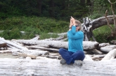 Jenny in Easy Pose (Sukhasana) with Eagle Arms (Garudasana) on a beach log at Schooner Beach, Pacific Rim National Park, Vancouver Island, B.C. (Photo by Amy Asay).