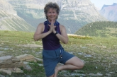 Jenny in Tree Pose (Vrikshasana) hands in prayer position (Anjali Mudra), along an interpretive trail at Logan Pass, Glacier National Park, Montana (Photo by Ian Hatter).