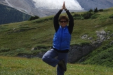 Jenny in a modified Tree Pose (Vrikshasana), evocative of a Standing Figure 4 Pose to accommodate her muddy hiking boots, with arms extended overhead and in prayer position, along the Wilcox Pass Trail, with the Athabasca Glacier behind, Jasper National Park, Alberta (Photo by Ian Hatter).