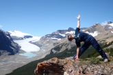 Jenny in Extended Triangle Pose (Utthita Trikonasana), gaze to the side, on Parker Ridge, Saskatchewan Glacier behind, Banff National Park (Photo by Ian Hatter).