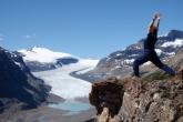 Jenny in Warrior One Pose (Virabhadrasana I) on Parker Ridge, with the Saskatchewan Glacier behind, Banff National Park, Alberta (Photo by Ian Hatter).