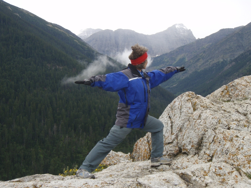 Jenny conjuring the clouds in Warrior Two Pose (Virabhadrasana II) on the Bear's Hump of Mount Crandell, with the Cameron Valley below, in Waterton Lakes National Park, Alberta, (Photo by Ian Hatter).