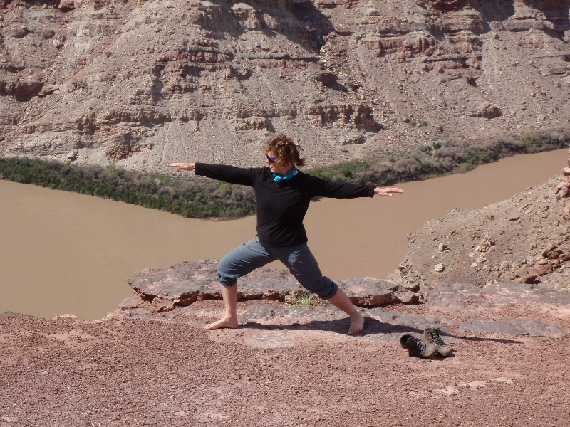 Jenny in Warrior Two Pose (Virabhadrasana II) above the confluence of the Green and Colorado rivers in Canyonlands National Park, Utah (Photo by Ian Hatter).